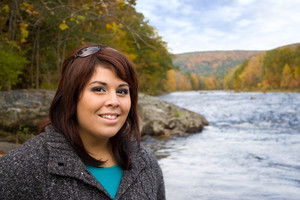 A young plus sized model posing by a river in New England during Autumn.
