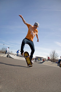 A young skateboarder doing a stunt in a skate park.