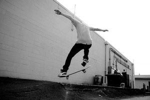 A young skateboarder doing a stunt in an urban area.