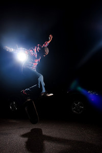 A young skateboarder doing jumping and kick flip tricks under dramatic rim lighting with lens flare.