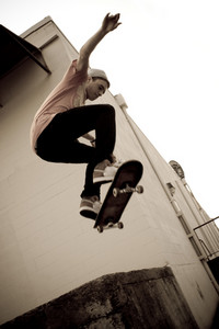 A young skateboarder launches off a concrete loading dock in an urban setting.