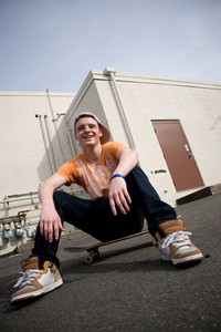 A young skater resting on his board.
