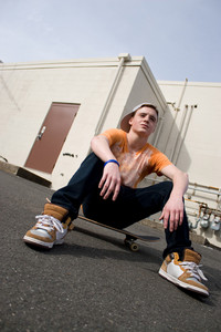 A young skater resting on his skateboard.