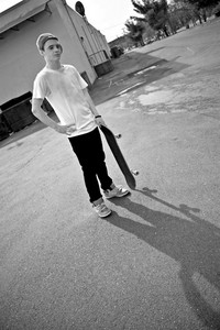 A young skater teen posing in an urban area with his board.