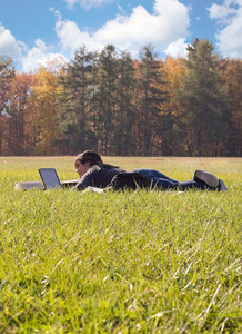 A young student using her laptop computer while laying in a green grassy field.