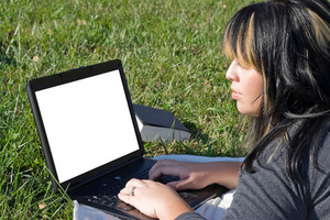 A young student using her laptop computer while laying in the grass on a nice day.  The screen area contains the clipping path.