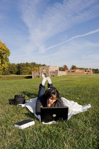 A young student using her laptop computer while laying in the grass on a nice day.