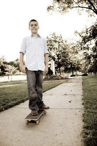 A young teenage boy standing on his skateboard in the park.  Sepia tone.