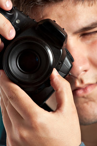 A young teenage photographer taking a photo with his DSLR camera. Shallow depth of field.