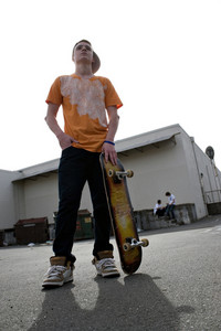 A young teenage skateboarding standing with his skateboard and other kids hanging out in the background.