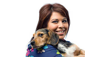 A young veterinarian holding a cute mixed breed beagle yorkie dog isolated on a white background with copy space.