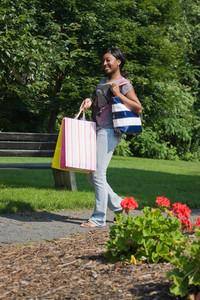 A young woman carrying her purse and shopping bags.