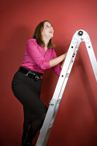 A young woman climbs a ladder over a red background.