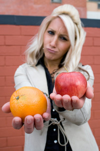 A young woman compares an apple to an orange.