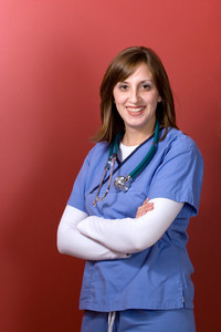 A young woman doctor with her arms crossed isolated over a red background