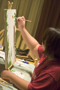 A young woman doing working with oil paints on canvas.