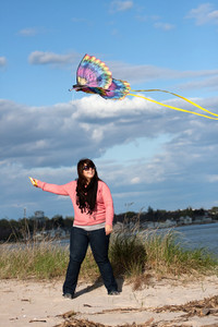 A young woman flies a kite at the beach on a nice day.