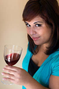 A young woman holding a glass of red wine.