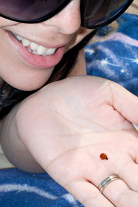 A young woman holding a ladybug in the palm of her hand at the beach.