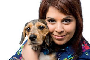 A young woman holding her cute mixed breed puppy isolated on a white background. The dog is half beagle and half yorkshire terrier.