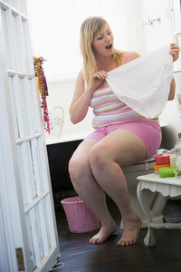 A young woman holding large underwear in the bathroom