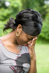 A young woman holds her hand on her forehead in anguish over pain or stress she is experiencing.