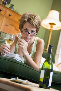 A young woman in her pyjamas drinking wine and smoking