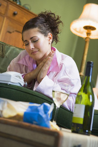 A young woman in her pyjamas drinking wine and watching her telephone