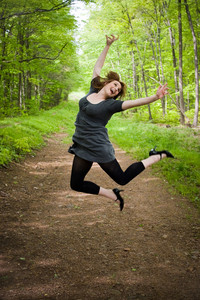 A young woman joyously jumping in the air in a wooded setting.