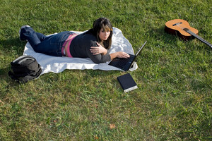 A young woman laying in the grass and using her laptop computer.  She could be a college student or even a musician.