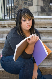 A young woman looks at her notebook in disgust.  She might have way too much homework to do.
