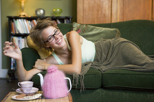A young woman lying on her couch eating biscuits