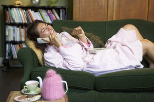 A young woman lying on her couch talking on the phone and eating chocolate