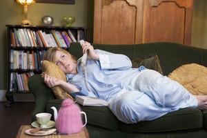 A young woman lying on her couch talking on the phone
