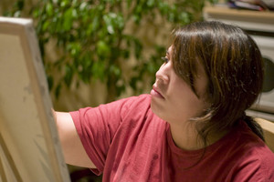 A young woman painting on a canvas.