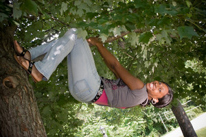 A young woman playfully hangs from a tree limb.