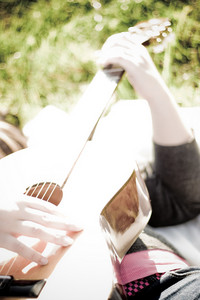 A young woman playing a guitar outdoors.