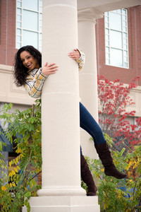 A young woman playing around on a large pillar outside.
