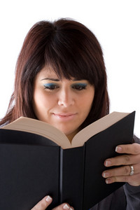 A young woman reading a book with a concerned expression on her face.