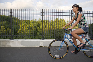 A young woman riding a bicycle across the bridge