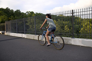 A young woman riding a bicycle across the bridge.
