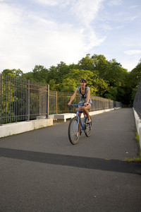 A young woman riding her bike outdoors.