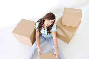 A young woman sitting and opened cardboard box looking at camera