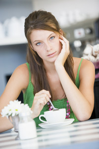A young woman sitting in a cafe drinking tea
