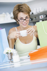 A young woman sitting in a cafe with shopping bags drinking tea