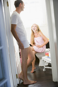 A young woman sitting in the bathroom wearing a towel and talking to a young man