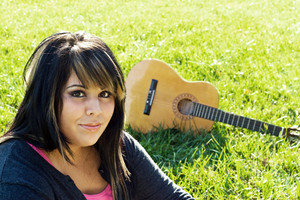 A young woman sitting in the green grass with an acoustic guitar in the background. Shallow depth of field.