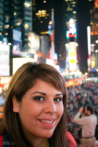 A young woman smiling as she stands in Times Square in New York City.