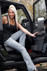 A young woman steps out of the passenger side door of a recreational vehicle.