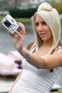 A young woman taking pictures of herself with a digital camera.  Shallow depth of field with focus on the camera.
